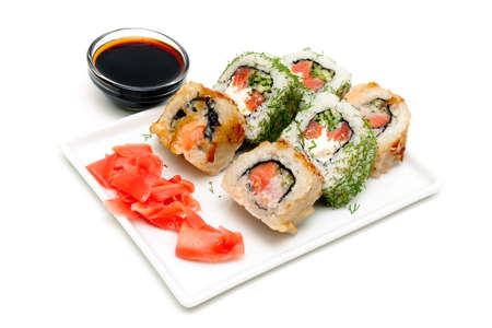 Japanese rolls on a plate with ginger and soy sauce. white background - horizontal photo.