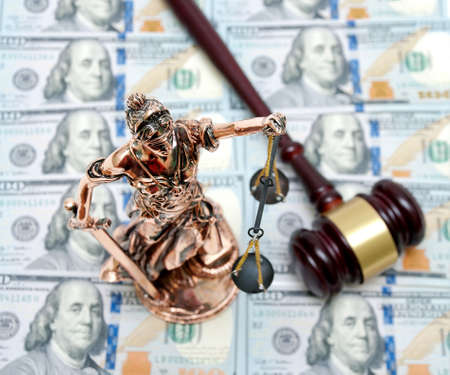 bronze statue of Justice on the background of dollar bills. top view - horizontal photo.