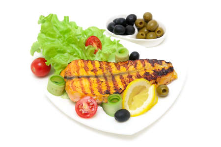 appetizing piece of baked salmon with lemon and vegetables on the plate on a white background. horizontal photo.