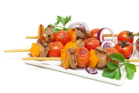 skewers of meat with vegetables on a plate close-up. white background - horizontal photo. Stock Photo