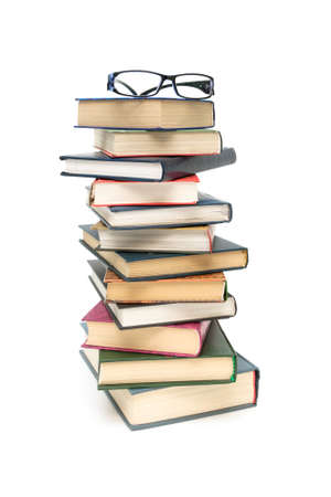 stack of books and glasses on a white background. vertical photo.