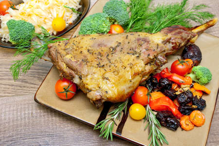 self made: baked leg of lamb with vegetables and herbs on a plate on a wooden table. horizontal photo. Stock Photo