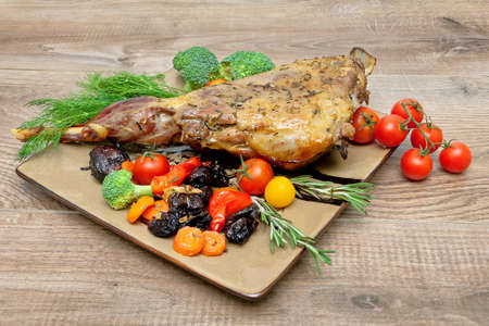 roasted leg of lamb with vegetables, greens and prunes on a plate on a wooden table. horizontal photo.