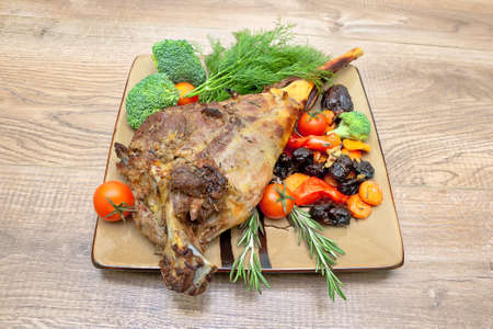 roasted leg of lamb with vegetables on a plate on a wooden table. horizontal photo.