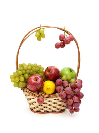 grapes, apples and lemon in a wicker basket. white background - horizontal photo.