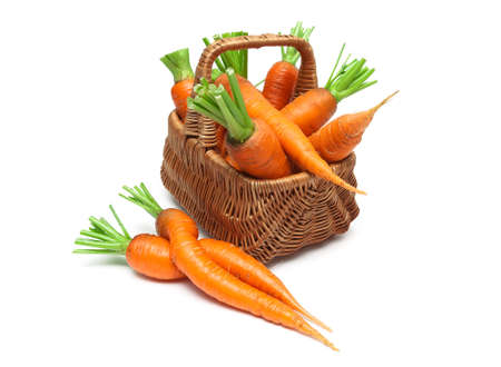 mature carrots in a wicker basket on a white background close-up. horizontal photo. Stock Photo