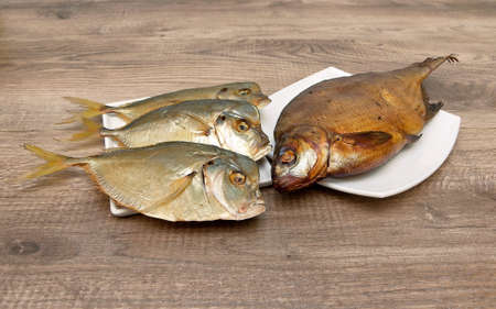 oceanic: Smoked and dried fish closeup on wooden background. Horizontal photo.