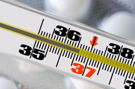 Thermometer shows the temperature of 36,6 man Stock Photo