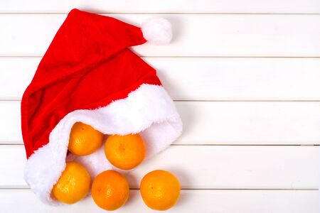 Christmas santa hat mandarins on a white wooden background