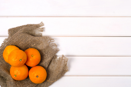 Mandarins cloth burlap on a white wooden background