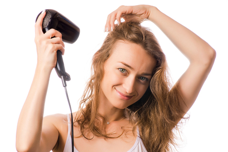 Beautiful young woman dries hair with a hairdryer beauty on white background isolation Stock Photo