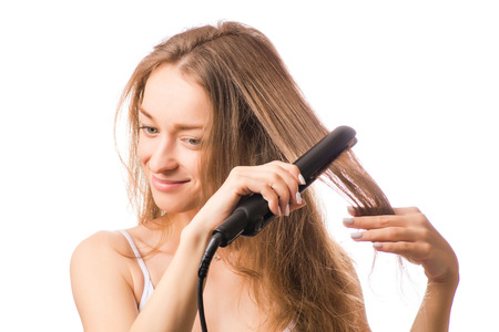Beautiful young woman hair ironing  on white background isolation