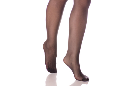Female legs black stockings tights on white background isolation