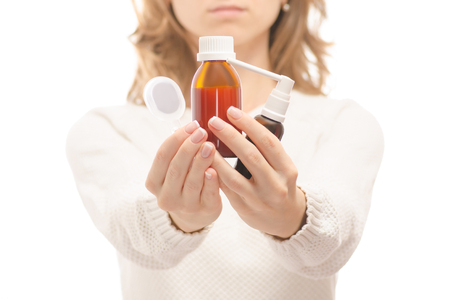 Woman in the hands of medicine syrup for throat spray on white background isolation Foto de archivo