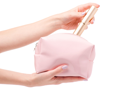 Pink open cosmetic bag in female hands with makeup brush on white background isolation Stockfoto