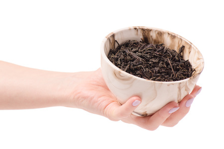 Leaf tea in a pial of female hands on a white background isolation Stock Photo