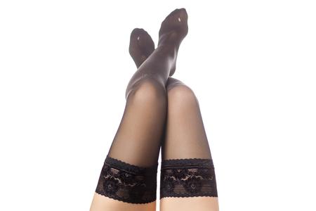 Vrouwelijke benen zwarte nylonkousen op een witte isolatie als achtergrond