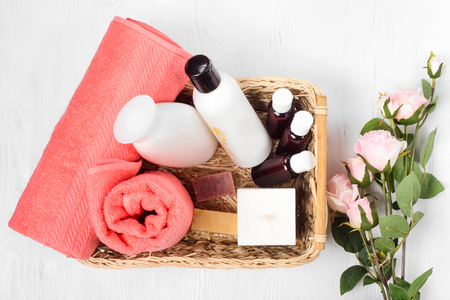 Towel cosmetics spa comb hair lotion candle flowers on white wooden background isolation Stockfoto