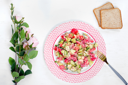 Plates of salad tomato cucumber cheese feta bread flowers on a white wooden background