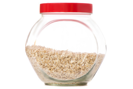 Capacity with a lid of flakes of oats on a white background isolation