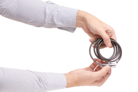 Mans hands the combination lock for a bicycle on a white background isolation Stock Photo