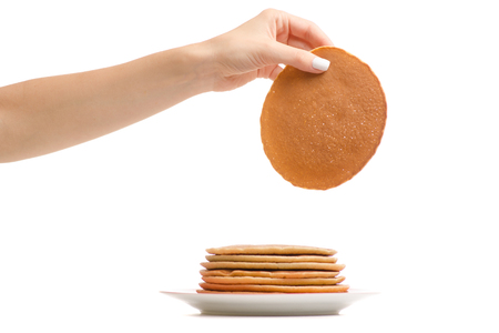 Female hand holding pancakes on a plate on a white background isolation