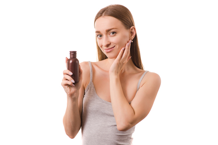 Beautiful young woman with a bottle for body and face oil lotion on white background isolation Imagens