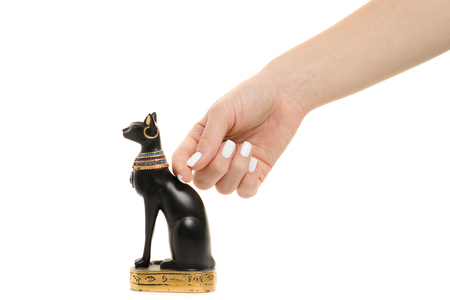 Female hand holding a cat statuette on a white background isolation
