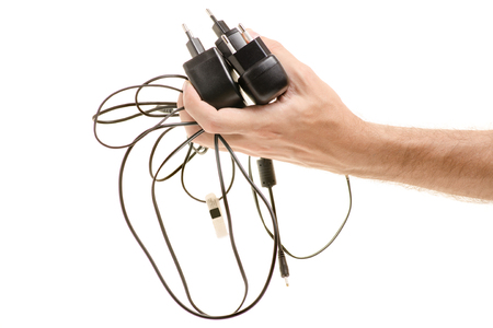 Old chargers on phones in male hands on white background isolation