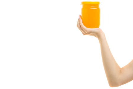 Honey jar in a female hand on a white background isolation