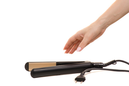 Hair iron in female hand on white background isolation