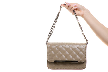 Female small gray lacquer bag on hand on white background isolation