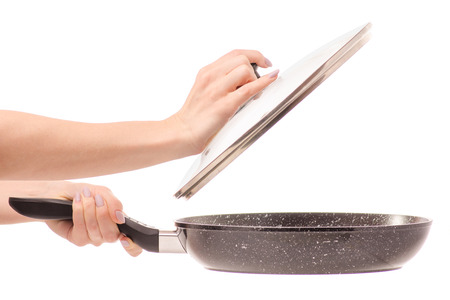 Frying pan with non-stick marble coating with lid female hand on white background isolation Stock Photo