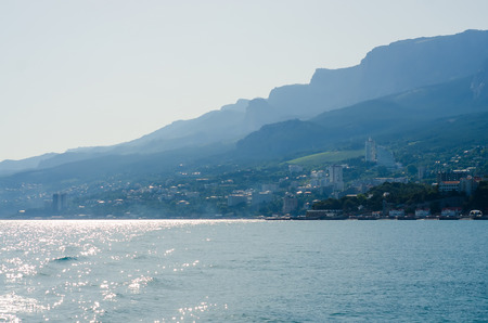 The city by the sea the sky is reflected in the water in the distance are seen the mountains Stock fotó