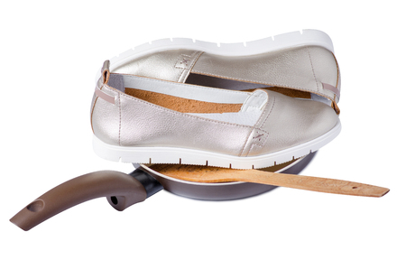 Female shoes in a frying pan cook on a white background isolation Stock Photo
