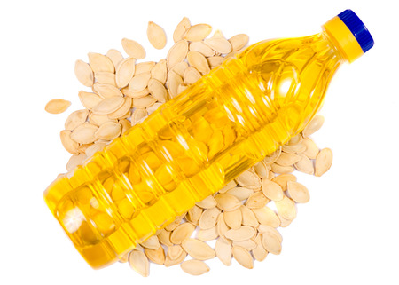 Pumpkin seeds and a bottle of oil on a white background, top view