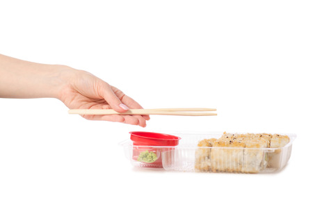 Set of rolls chopsticks for sushi in hand ginger wasabi soy sauce on white background isolation 版權商用圖片