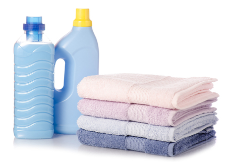 A stack of towels softener conditioner liquid laundry detergent on white background isolation Foto de archivo