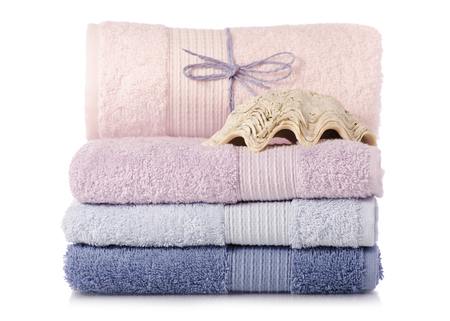 A stack of towels pink blue spa sea seashell stones on a white background isolation