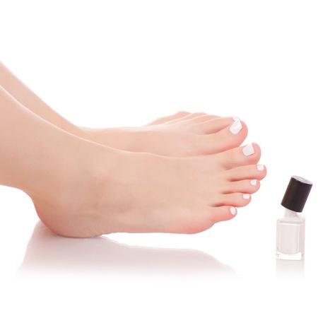 Weibliche Füße Beine Nagellack in weißen Händen auf einem weißen Hintergrund Isolation