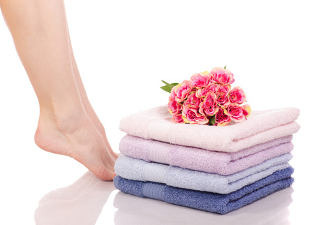 Female feet legs heels color bath towels flower beauty spa on a white background isolation Standard-Bild