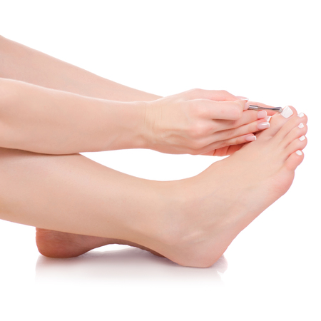 Female feet legs pusher for nails in hands pedicure beauty on white background isolation 스톡 콘텐츠