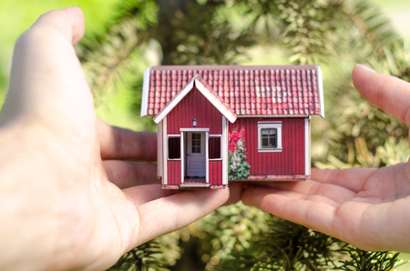 Small house in two hands nature tree green background