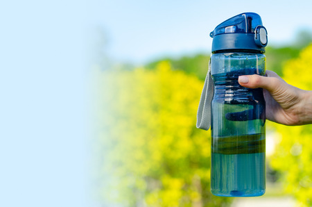 Bottle with water and lemon in hand on grass spring nature blur background