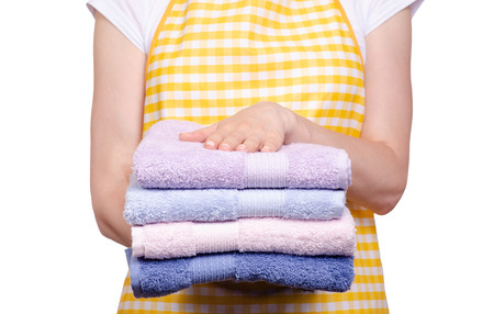 Woman in apron in hands stack towels on white background isolation
