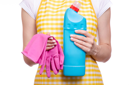 Woman in apron in hands cleaning glove and domestic toilet detergent household chemicals on white background isolation