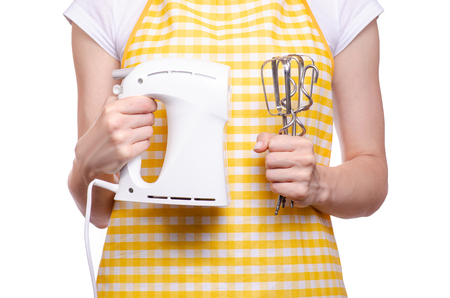 Woman in apron in hands of electric kitchen mixer on white background isolation
