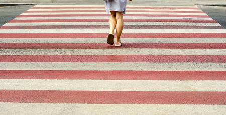A woman crosses a pedestrian crossing street road