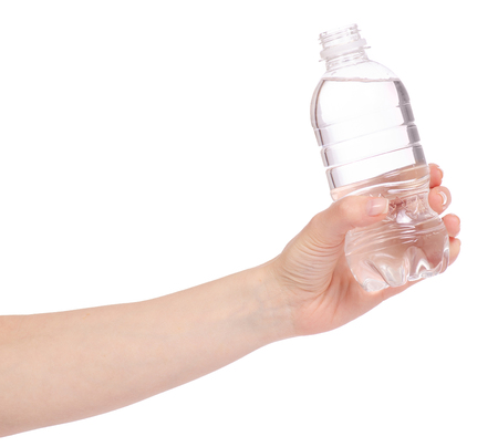 A bottle of water in hand on a white background is isolated
