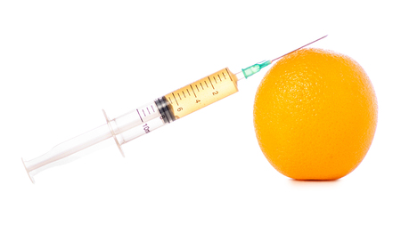 Syringe of orange on a white background isolation Фото со стока